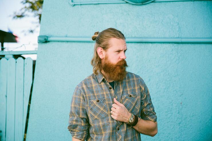 A gentleman with a robust red, beard and plaid shirt poses in front of a blue wall.